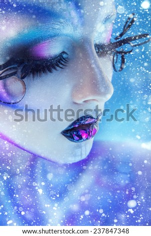 Charming portrait of female with creative body art closed eyes and snow on background in studio - stock photo