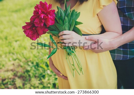 charming pregnant woman with her husband holding red flowers at sunset - stock photo