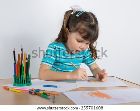 Charming preschooler with pigtails draws at table. Little girl draws - stock photo