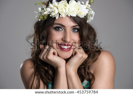 Charming pretty young woman with head in hands pose smiling and looking at camera over gray studio background - stock photo