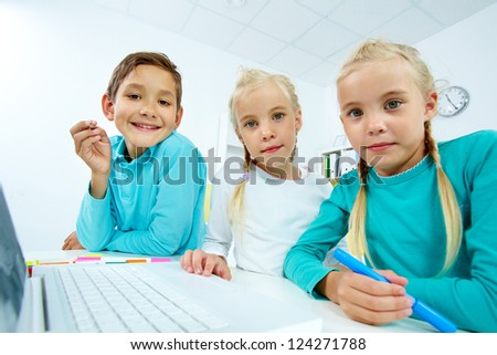 Charming pupils using modern means of communication - stock photo