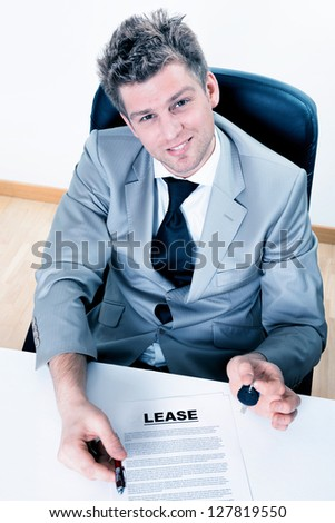 charming real estate agent proposes to sign a lease with handing over the keys - stock photo