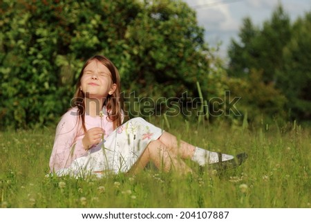 Charming Russian girl sitting in the green grass on a summer day, Russia, Zelenograd