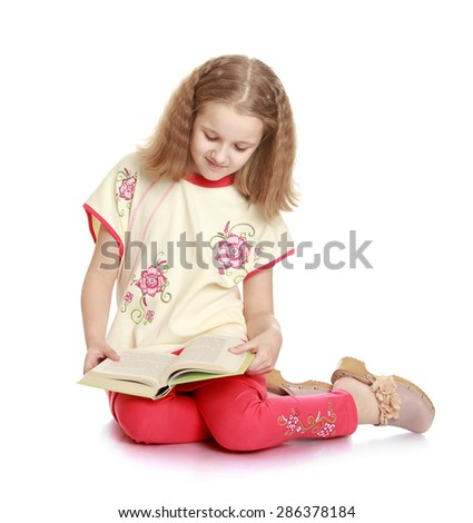 Charming schoolgirl reading a good book sitting on the floor-Isolated on white background - stock photo