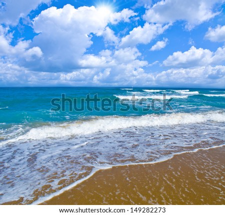 Charming seascape with beach, sky, clouds and sun.