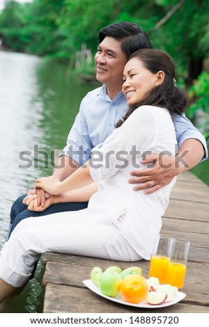 Charming senior couple cuddling on the riverside - stock photo