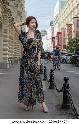 Charming sensual woman in fashionable gauzy clothing is posing at a town street with cars and people at blurred background - stock photo