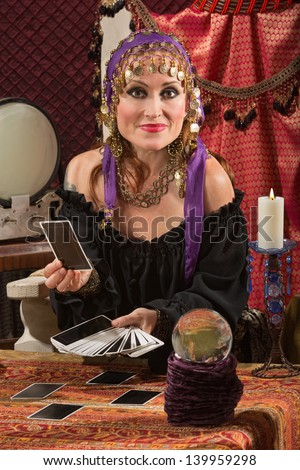 Charming sexy European tarot card reader in headscarf - stock photo
