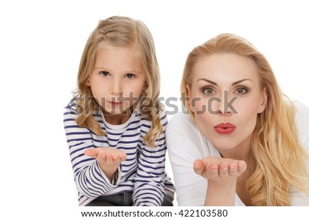 Charming. Shot of beautiful mother and daughter looking to the camera blowing kisses at the studio on white background. - stock photo