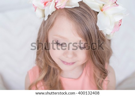 Charming sincere smiling blonde girl in orchid floral hairband wreath looking down portrait - stock photo