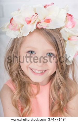 Charming sincere smiling blonde girl in orchid floral hairband wreath portrait - stock photo