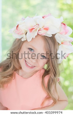 Charming sincere smiling blonde girl in orchid floral hairband wreath portrait with green background - stock photo
