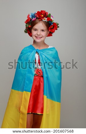 Charming smiling child with a happy smile in a national Ukrainian suit holding a big flag of Ukraine on a gray background on Independence Day - stock photo
