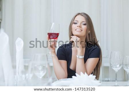 Charming smiling girl drinking wine in restaurant - stock photo