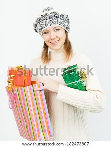 Charming smiling girl in winter cap holding a gift box