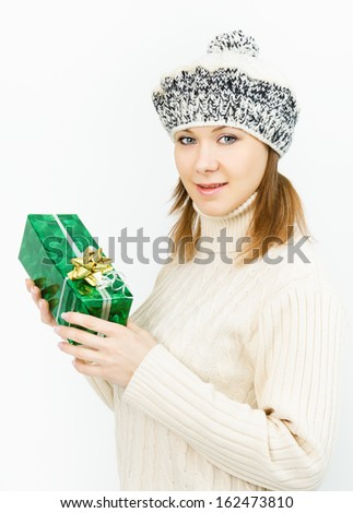 Charming smiling girl in winter cap holding a gift box - stock photo