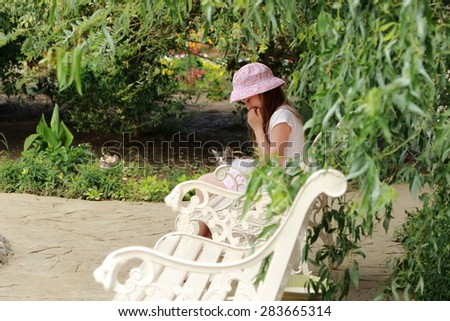 Charming smiling little girl in panama hat sits on a wooden bench holding little kitten in the summer garden outdoor - stock photo