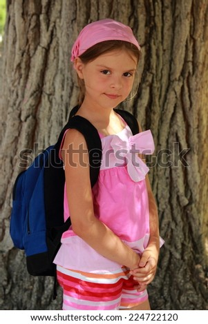 Charming smiling little girl with a backpack on a wood background on the theme of tourism and a healthy lifestyle - stock photo