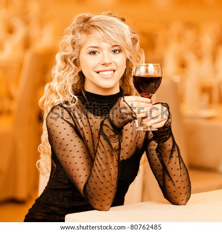 Charming smiling young woman in black clothes with red wine glass sits at magnificent restaurant.