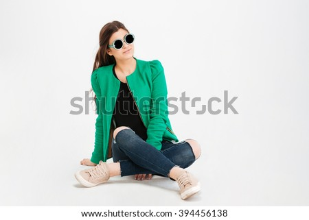 Charming smiling young woman in green jacket and ripped jeans and sunglasses sitting over white background - stock photo