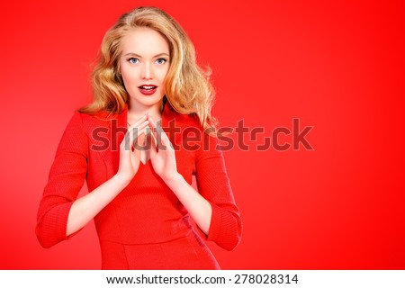 Charming smiling young woman in red dress and with blonde curled hair. Beauty, fashion. Cosmetics, make-up. Red background. - stock photo