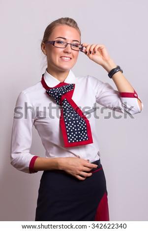 Charming Stewardess Dressed In Blue Uniform On Gray Background - stock photo