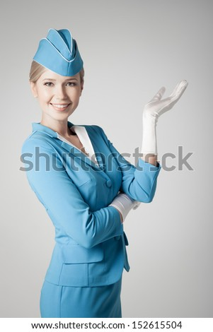 Charming Stewardess Dressed In Blue Uniform Pointing On Gray Background - stock photo