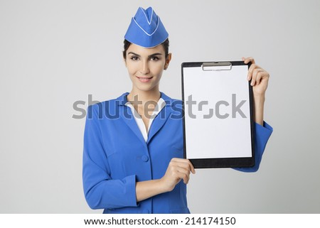 Charming Stewardess Dressed In Blue Uniform with empty blank in hands. - stock photo
