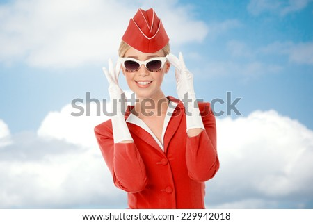 Charming Stewardess Dressed In Red Uniform And Vintage Sunglasses. Sky With Clouds Background. - stock photo
