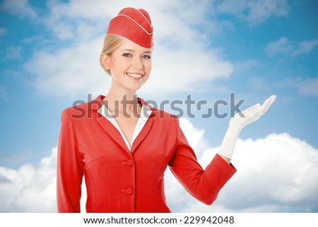 Charming Stewardess Dressed In Red Uniform Holding In Hand. Sky With Clouds Background. - stock photo