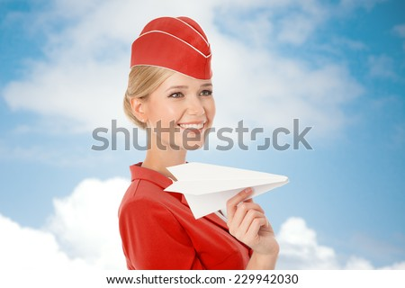 Charming Stewardess Holding Paper Plane In Hand. Sky With Clouds Background. - stock photo