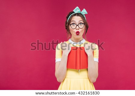Charming surprised pinup girl in glasses standing and holding red book over pink background - stock photo