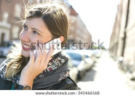 charming sweet caucasian girl on her phone in the urban scene - stock photo