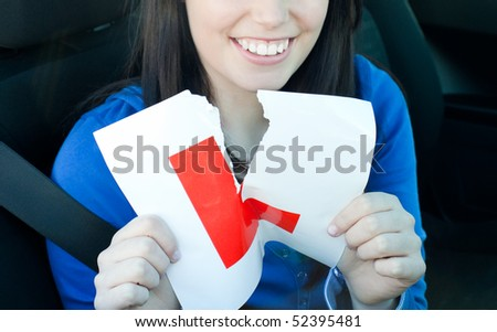 Charming teen girl sitting in her car tearing a L-sign after having her driver's licence - stock photo