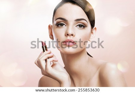 Charming teen girl woman with lipstick / photoset of attractive brunette girl on blurred beige background with bokeh   - stock photo