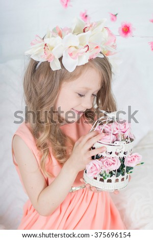 Charming tender pretty blonde caucasian girl in orchid floral hairband wreath holds cell with flowers and looks down - stock photo