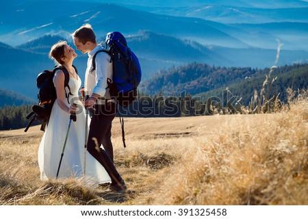 Charming tourist wedding couple hugs on the top of mountain. Honeymoon in Alps - stock photo