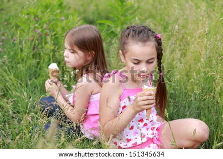 Charming two young girls eat ice cream and lie on the grass outdoor - stock photo