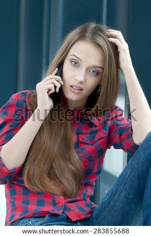 Charming upset girl talking over the phone - stock photo