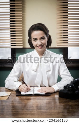 Charming vintage receptionist working at office desk, writing down appointments on a notebook