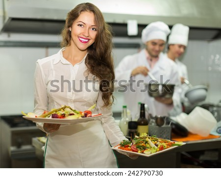Charming waitress take plates with prepared meal - stock photo