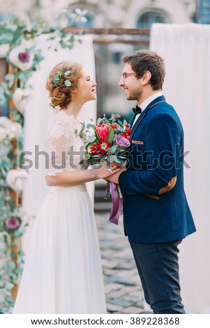Charming wedding couple lovingly looking on each other on the wedding ceremony - stock photo