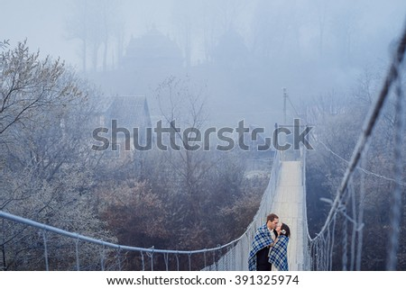 Charming wedding couple wrapped in blanket softly kiss on the sospension bridge at mountains. Autumn mountains background - stock photo