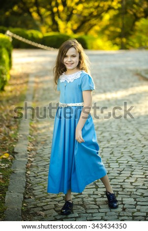 Charming white little girl with loose dark hair in vintage blue long dress and black shoes posing on cobbled walkway background in day at park, vertical picture - stock photo