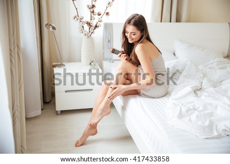 Charming woman applying cream on legs on the bed at home - stock photo