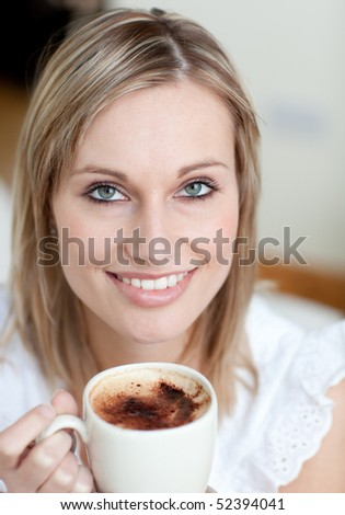 Charming woman drinking a coffee sitting on a sofa at home