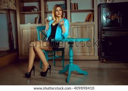charming woman drinking tea with a cookies over blue table and looking away