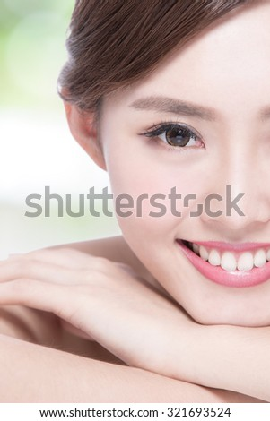 Charming woman face Smile to you close up while lying with green background, asian girl - stock photo