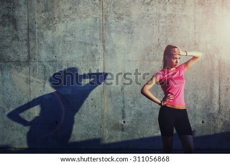 Charming woman holding hand at forehead while standing against of gray wall with its own shadow - stock photo