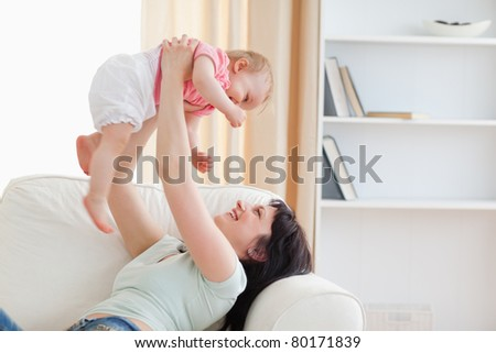 Charming woman holding her baby in her arms while sitting on a sofa in the living room - stock photo